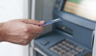 Hand inserting ATM card into bank machine to withdraw money. bus
